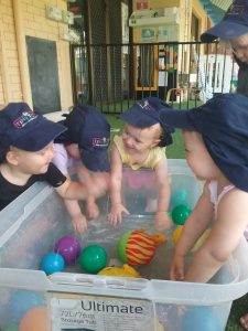toddlers at childcare reaching for balls in shallow plastic tub of water