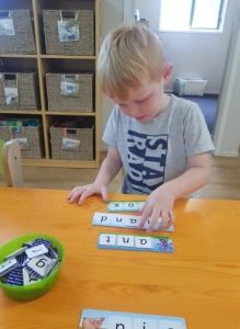 young boy at childcare spelling words with plastic cards