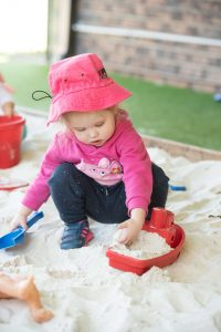 young girl playing in a sandpit at childcare